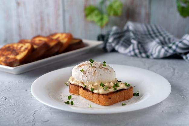 Gepocheerd ei met mayonaise en microgreens in een bord