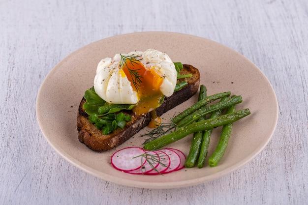 Gepocheerd ei op een stuk brood met gebakken sperziebonen, radijs en rucola op een bord