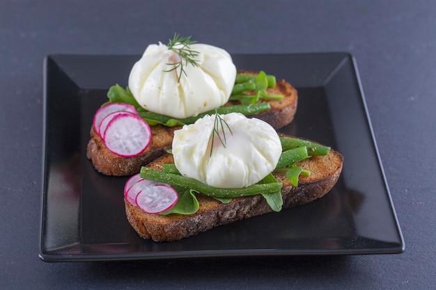 Gepocheerd ei op een stuk brood met gebakken sperziebonen, radijs en rucola