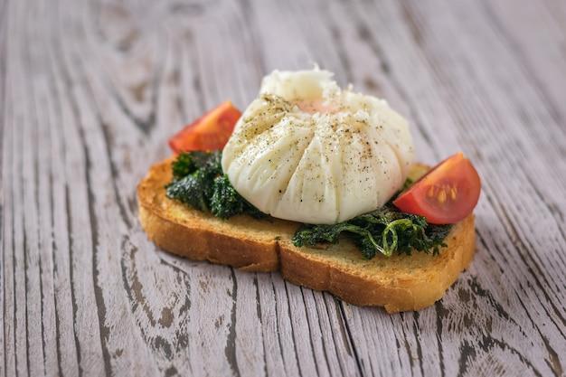Gepocheerd ei op een stuk geroosterd brood met plakjes tomaten. vegetarische snack met gepocheerde eieren.