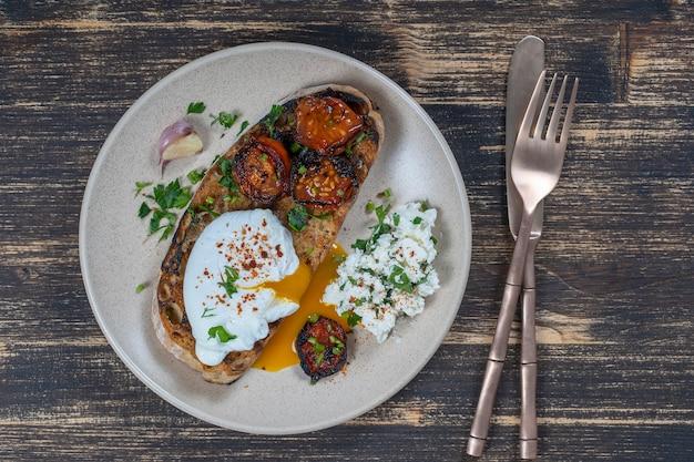 Gepocheerd ei op een stukje brood met gebakken rode tomaat, knoflook en kwark op een bord, close-up, bovenaanzicht