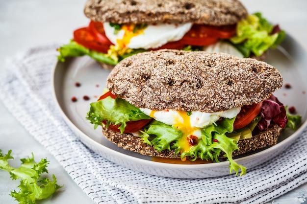 Gepocheerde ei sandwich met roggebroodje en tomaat op grijze plaat.