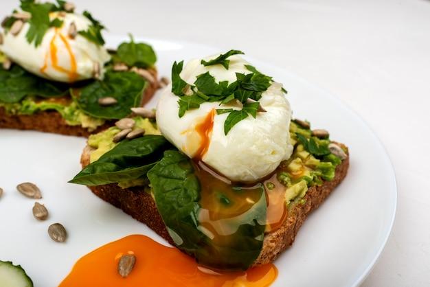 Gepocheerde eieren met avocado, spinaziebladeren en zaden op toastbrood op een witte plaat