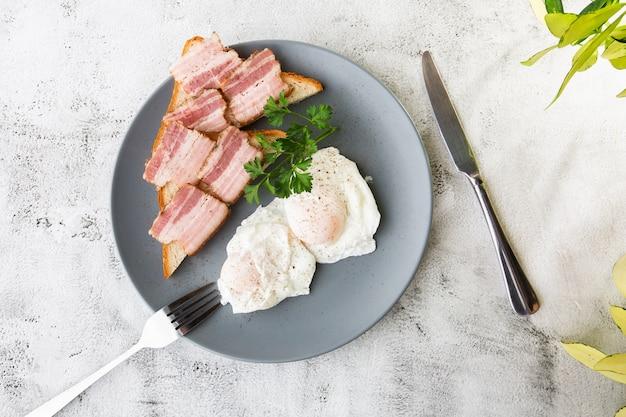 Gepocheerde eieren met spek op zuurdesem toast. geïsoleerd op witte marmeren achtergrond. zelfgemaakt eten. lekker ontbijt. selectieve aandacht. hotizontal foto.