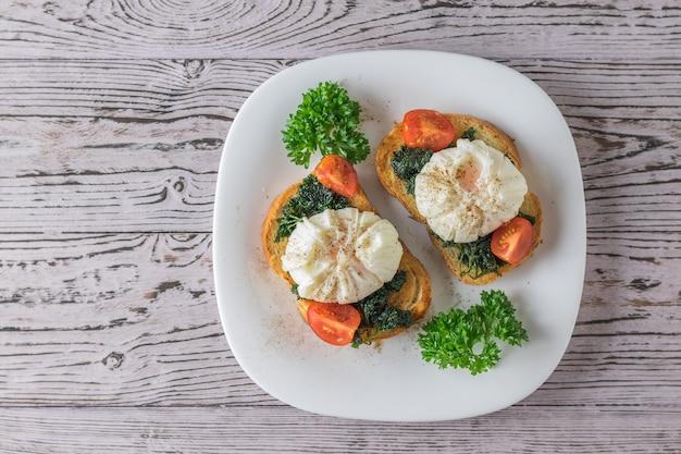Gepocheerde eieren op geroosterd brood met kruiden in een witte plaat. vegetarische snack met gepocheerde eieren. het uitzicht vanaf de top.