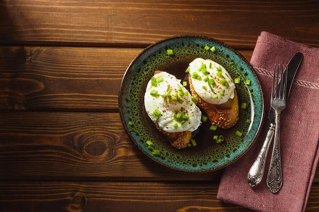 Gepocheerde eieren op stokbrood met greens