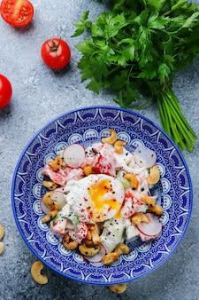 Gepocheerde eiersalade met groenten en cashewnoten. groentesalade bovenaanzicht met ingrediënten