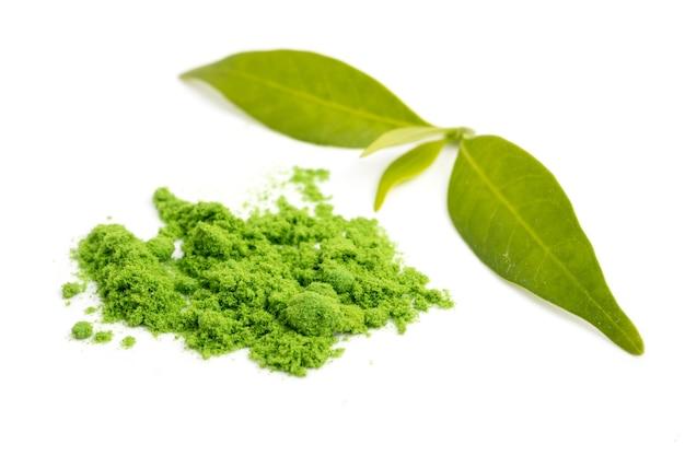 Gepoederde groene thee met blad op witte achtergrond.