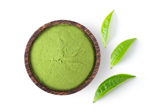 Gepoederde matcha groene thee in kom en bladeren op witte muur.