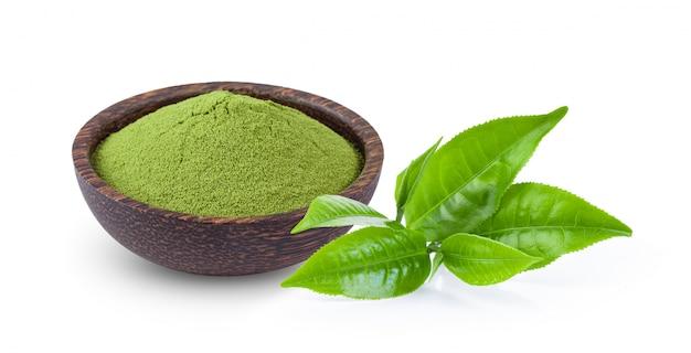 Gepoederde matcha groene thee in kom met blad dat op wit wordt geïsoleerd
