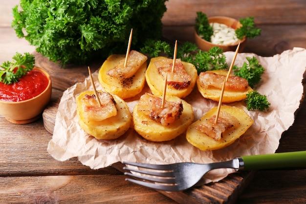 Gepofte aardappel met spek op houten snijplank, op houten achtergrond