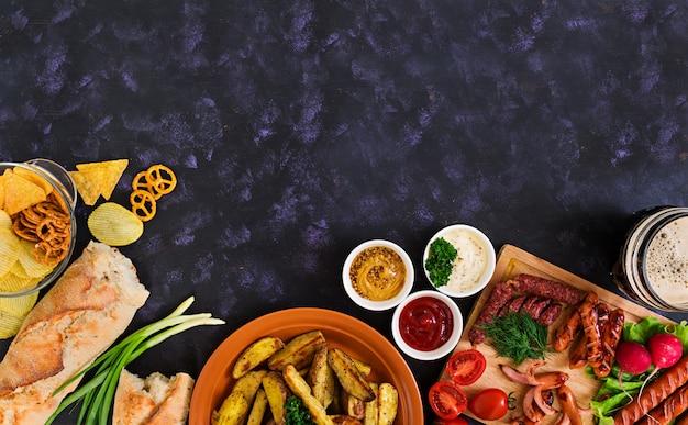 Gepofte aardappelpartjes met worstjes en kruiden.