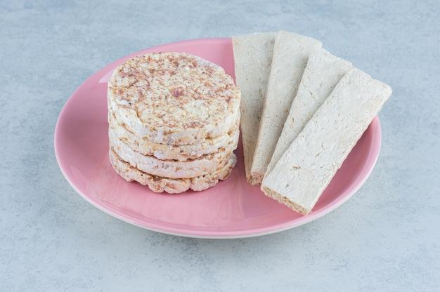 Gepofte rijstwafels en zoete cracker in de plaat op marmer.