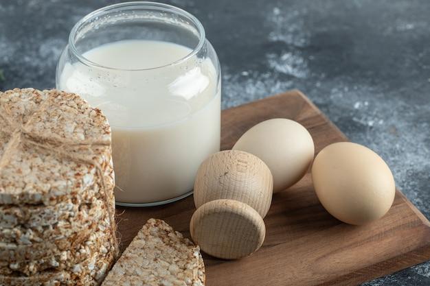 Gepofte rijstwafels, melk en eieren op een houten bord