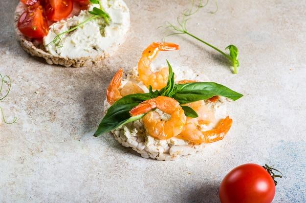 Gepofte rijstwafels met garnalen en avocado aan boord. snack met zeevruchten. knäckebröd, broodkorstjes. dieet voedsel concept. basilicum. gezond eten. gezond ontbijt. cherry-tomaten. biologisch voedsel