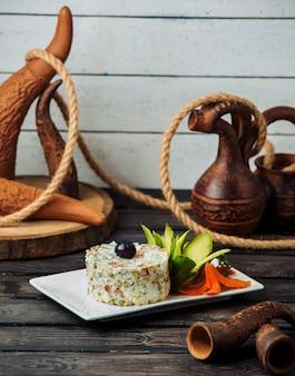 Geportioneerde olivier salade gegarneerd met komkommer en wortelbloemen