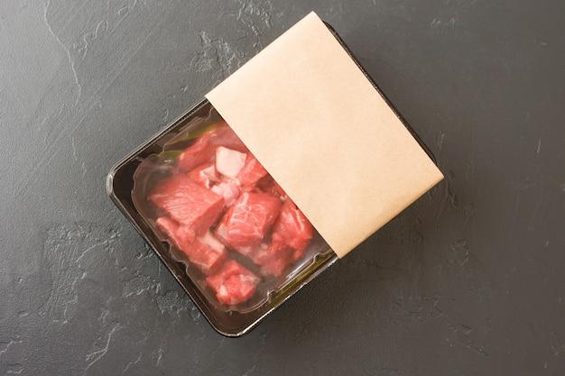 Geportioneerde stukjes vers vlees in vacuümverpakking op een zwarte achtergrond. bovenaanzicht. ontwerp van de lay-out van het logo. het concept van snel koken.