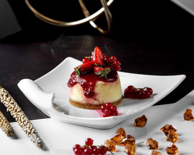 Gepporteerde cheesecake gegarneerd met bessen en jam