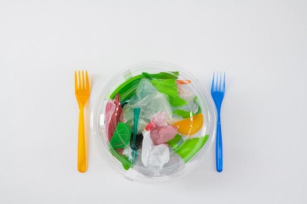 Geprepareerde vork in de buurt. transparante verpakking met afval en plastic zakken erin als letterlijke maaltijd voor ons milieu