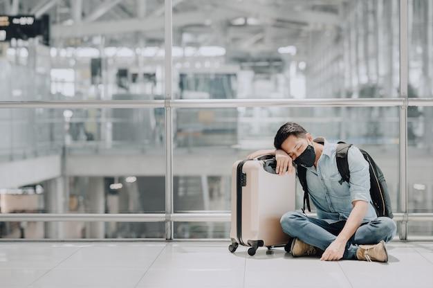 Geprobeerd aziatische man met gezichtsmasker rusten of slapen op de vloer van de luchthaventerminal