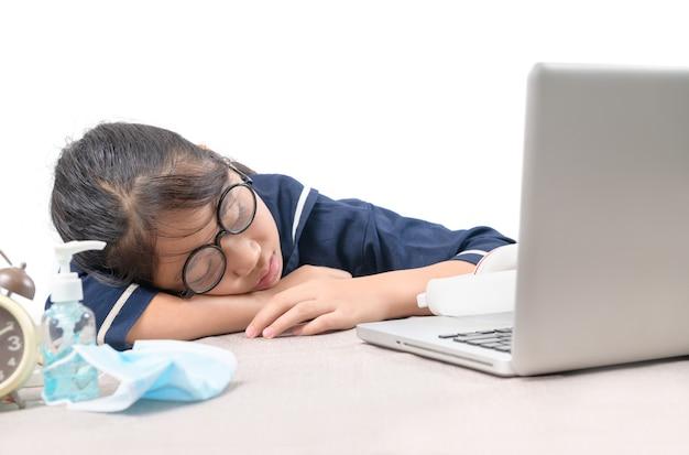 Geprobeerd student viel in slaap terwijl huiswerk met de geïsoleerde laptop, onderwijsconcept