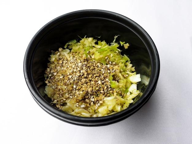Gepureerde verse korianderwortel met knoflook en zwarte pepers in zwarte kom, thaise kruideningrediënten voor het koken van heerlijk voedsel