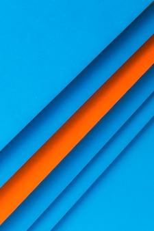 Gerangschikt gestreepte blauw en een oranje papier achtergrond