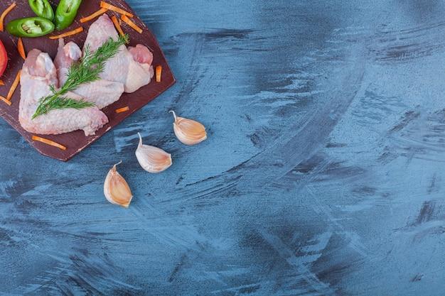 Geraspte groenten en kippenvleugels op een snijplank, op het blauw.
