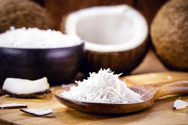 Geraspte houten lepel van kokosnoot, ingrediënt op basis van kokosnoot Premium Foto