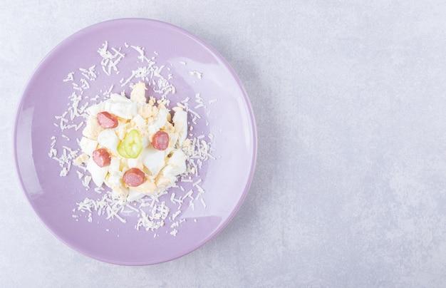 Geraspte kaas en ei met worstjes op paarse plaat.