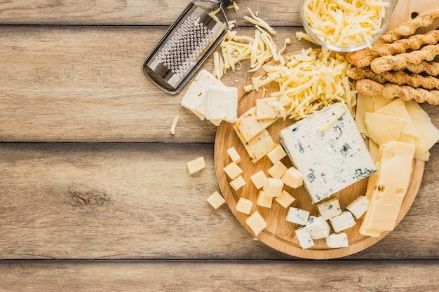 Geraspte kaas, kaasblokken en broodstokken boven het bureau