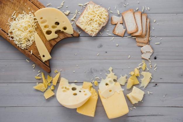 Geraspte kaas met plakjes en brood op grijs houten bureau