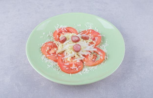Geraspte kaas met worstjes en tomaat op groene plaat.