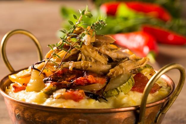 Geraspte kip met aardappelpuree en groenten geserveerd in de tafel