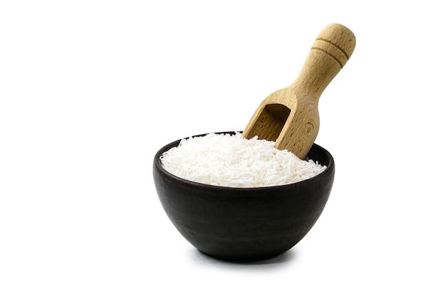 Geraspte kokosnoot, culinair ingrediënt in rustieke aardewerken kom met maatlepel, geïsoleerde witte achtergrond