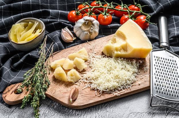 Geraspte parmezaanse kaas en metalen rasp op houten snijplank. grijze achtergrond. bovenaanzicht.