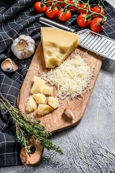 Geraspte parmezaanse kaas en metalen rasp op houten snijplank