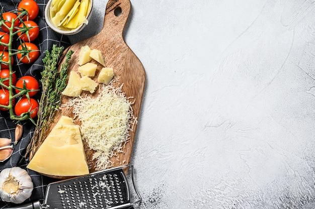 Geraspte parmigiano reggiano kaas en metalen rasp