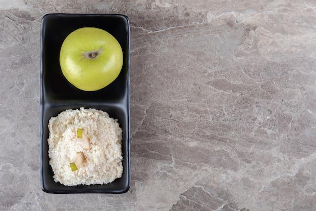 Geraspte rijstwafel en appel in de kom, op het marmeren oppervlak