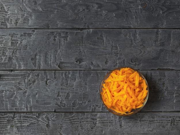 Geraspte verse wortelen in een glazen kom op een donkere rustieke tafel