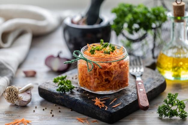 Geraspte verse wortelsalade met kruiden in een glazen pot