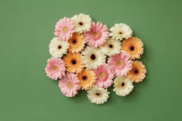 Gerbera bloemen op de achtergrond van een groenboek. lente samenstelling. lay-out voor ansichtkaart voor moederdag of 8 maart. plat leggen