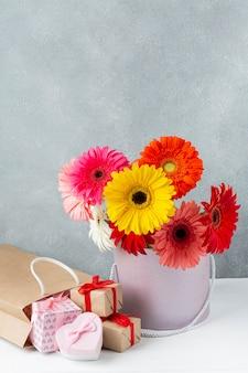 Gerbera madeliefjebloemen in een emmer met kleine geschenkdozen in de buurt