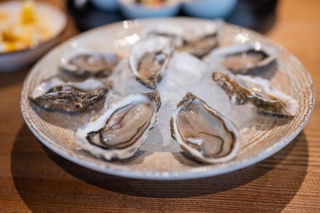 Gerecht oesters open met citroen en saus rauw in een restaurant met ijs