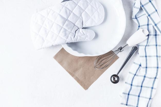 Gerechten en keukenaccessoires voor het bakken op de keukentafel op een witte achtergrond