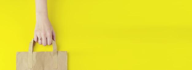Gerecycleerde bruine papieren boodschappentas met handvat in de hand op gele achtergrond, plat gelegd, mockup