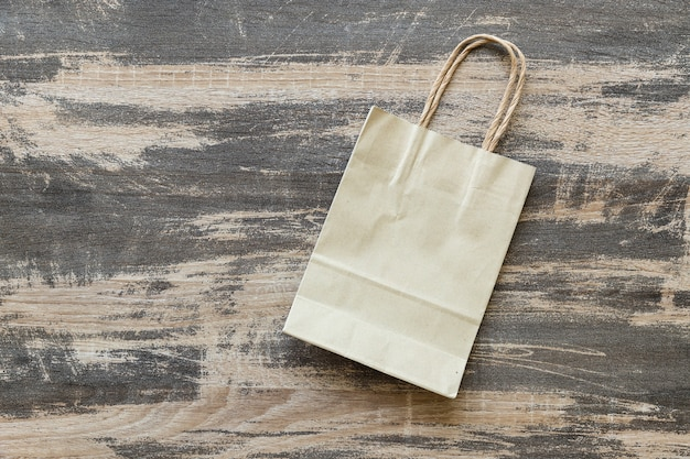 Gerecycleerde papieren zak op oude houten ondergrond, milieuvriendelijk en duurzaamheidsconcept