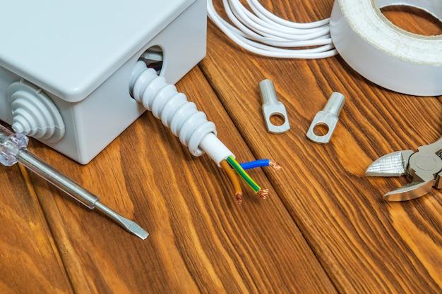 Gereedschap en accessoires gebruikt bij elektrische installatie of reparatie op een houten werkplaatstafel