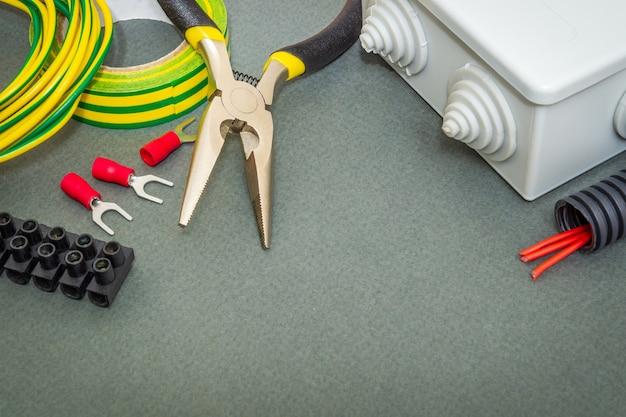 Gereedschap en accessoires gebruikt bij elektrische installatie op een grijze werkplaatstafel