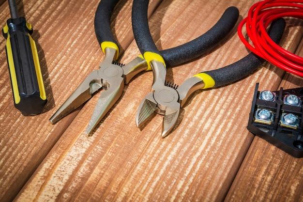 Gereedschap en reserveonderdelen voor meester-elektricien op vintage houten planken
